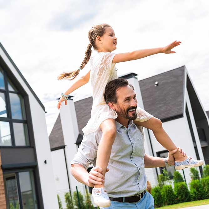 Familie vor ihrem modernen Wohnhaus
