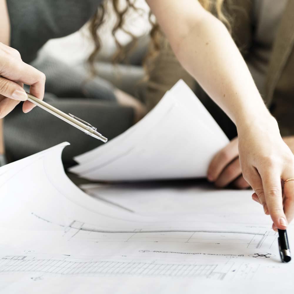 Innenarchitekt deutet auf einen Bauplan auf dem Schreibtisch