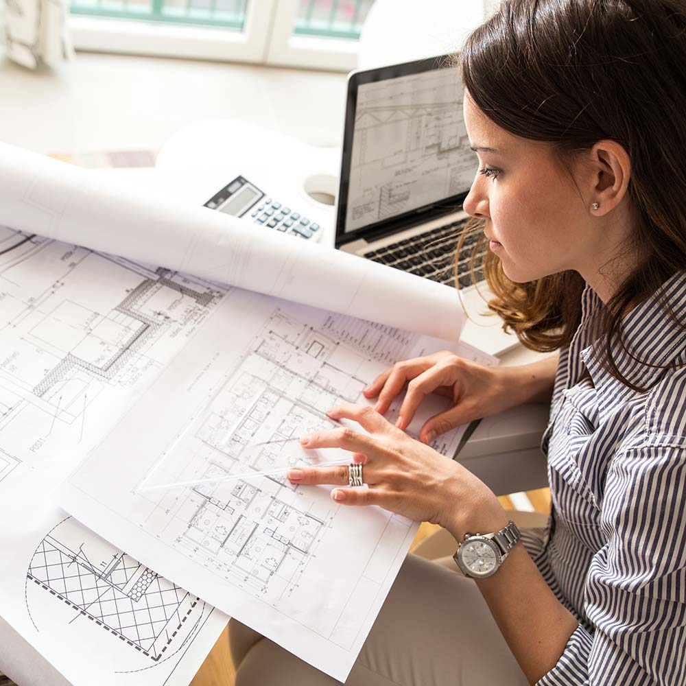 roomarts - Innenarchitektin arbeitet am Schreibtisch an einem Bauplan
