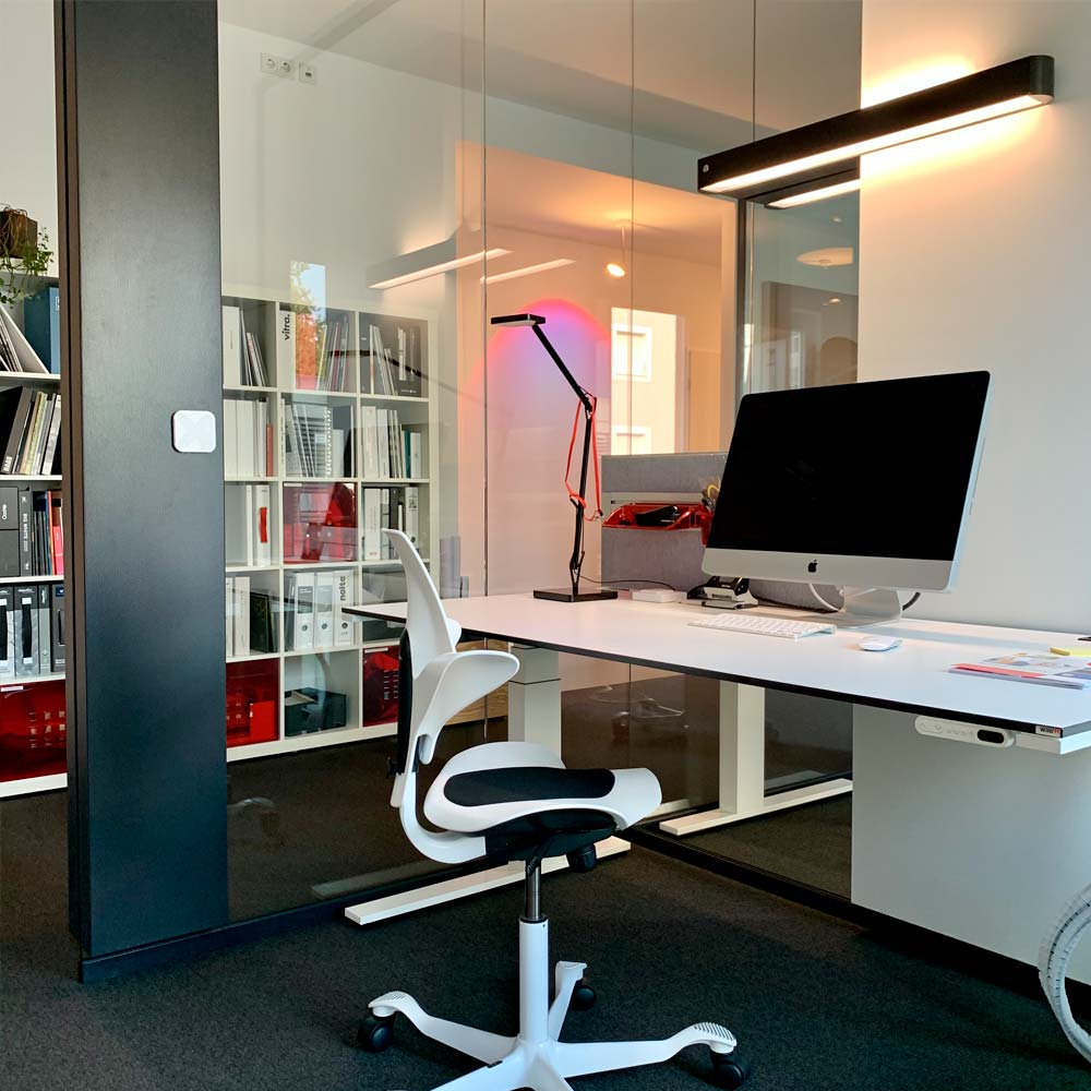 Wohnflächenberechnung von roomarts - Frau sitzt am Schreibtisch mit einem Bauplan